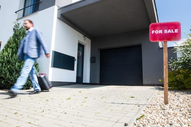 Man die het huis verlaat tijdens een ecnomische crisis, een gezinswoning te koop, mensen zonder geld