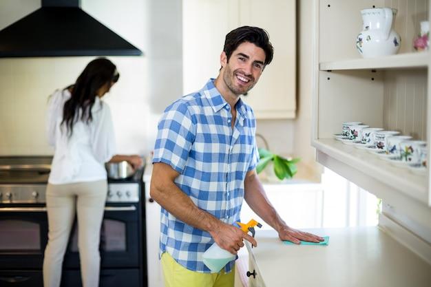 Man die het keuken en vrouwen kokende voedsel op achtergrond schoonmaken