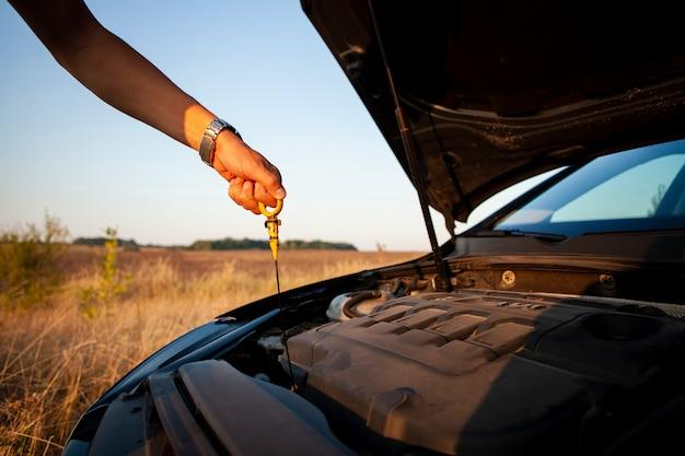 Man die het oliepeil van de motor controleert