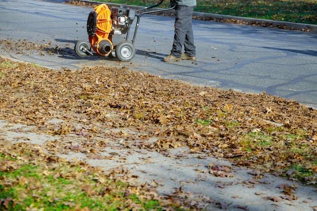 Man die het trottoir met een bladblazer in de herfst schoonmaken