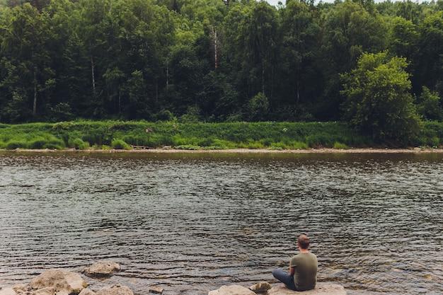 Man die het uitzicht op het meer en de natuur bewondert