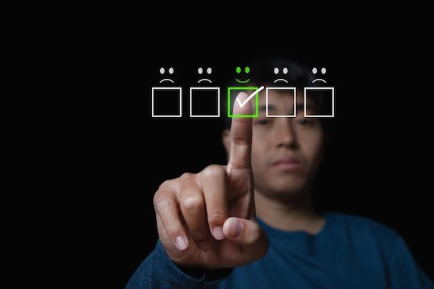 Man die het virtuele scherm op het smileygezichtspictogram op het digitale aanraakscherm aanraakt. evaluatieconcept van de klantenservice.
