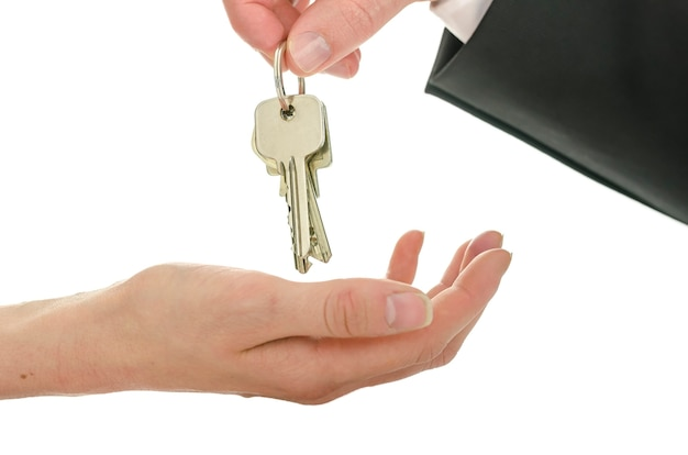 Man die huissleutels overhandigt aan een nieuwe eigenaar. geïsoleerd op witte achtergrond.