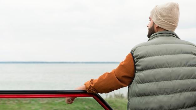 Man die in de buurt van auto in de natuur