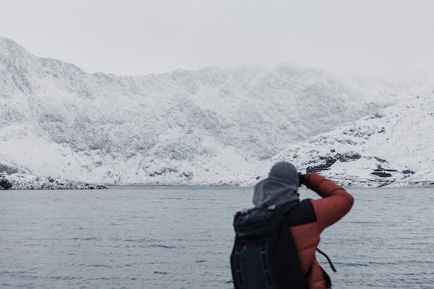 Man die in de winter bij een meer staat