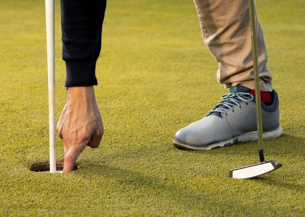 Man die in het gat van de golfbal met de hand bereikt
