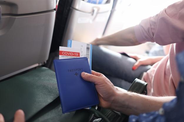 Man die in het vliegtuig vliegt en een immunisatiepaspoort vasthoudt tegen covid 19 en tickets close-up