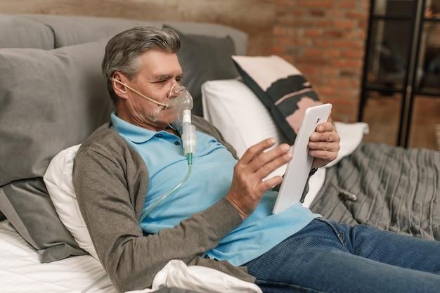 Man die inademing doet door zuurstofmasker in de slaapkamer thuis en laptop gebruikt.