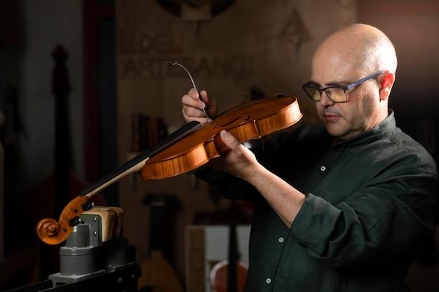 Man die instrumenten maakt in zijn atelier alleen
