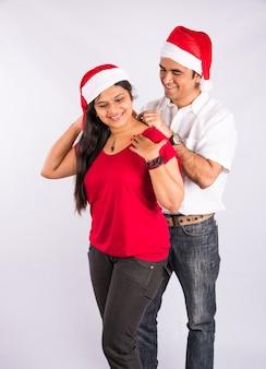 Man die ketting op de nek van de vrouw plaatst in de kersttijd, indiase man die ketting cadeau doet aan vrouw van vriendin met kerst, aziatisch stel en ketting cadeau doet