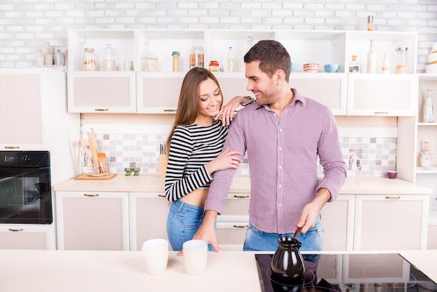 Man die koffie maakt voor zijn vriendin in de keuken