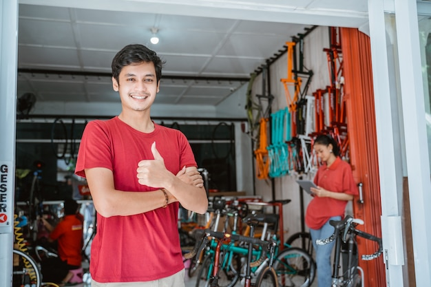 Man die lacht met duimen omhoog in fietsenwinkel