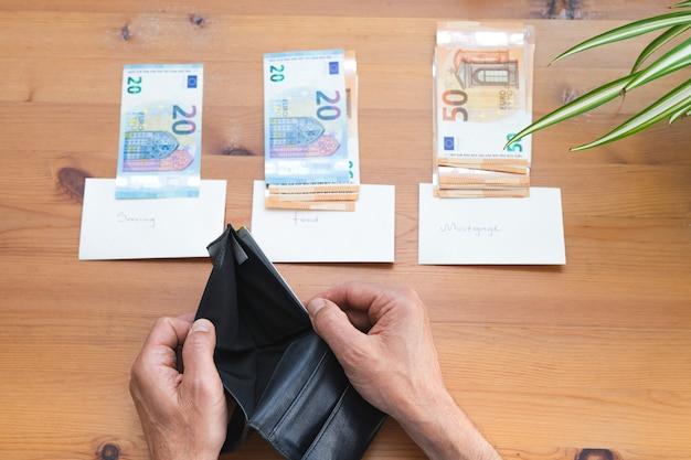 Man die lege portemonnee toont na het verdelen van al het geld voor maandelijkse uitgaven. ruimte kopiëren. economie en crisisconcept.