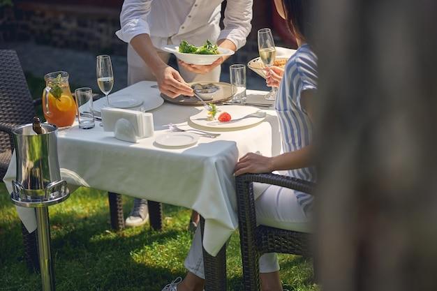 Man die maaltijd op het bord van de vrouw zet terwijl de vrouw een glas wijn vasthoudt