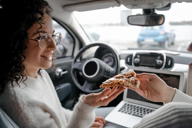 Man die meisje een stuk pizza in de auto voedt. gelukkig krullend jonge vrouw bril dragen en glimlachen. paarontspanning in de autocabine. concept van samen genieten van tijd