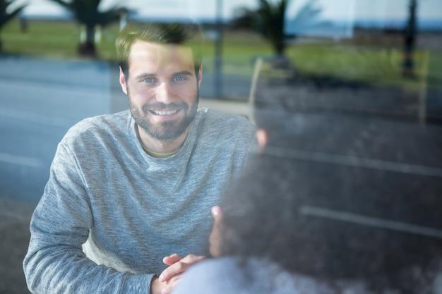 Man die met een vrouw in koffiewinkel spreekt