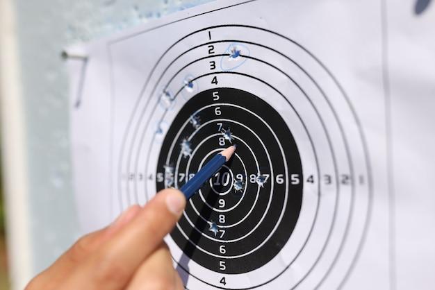Man die met potlood naar schoten op papier doel close-up toont