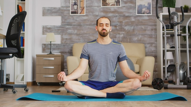 Man die mindfulness beoefent op yogamat in een gezellige woonkamer.