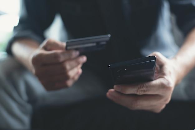 Man die mobiele telefoon en creditcard gebruikt voor mobiel bankieren en online winkelen