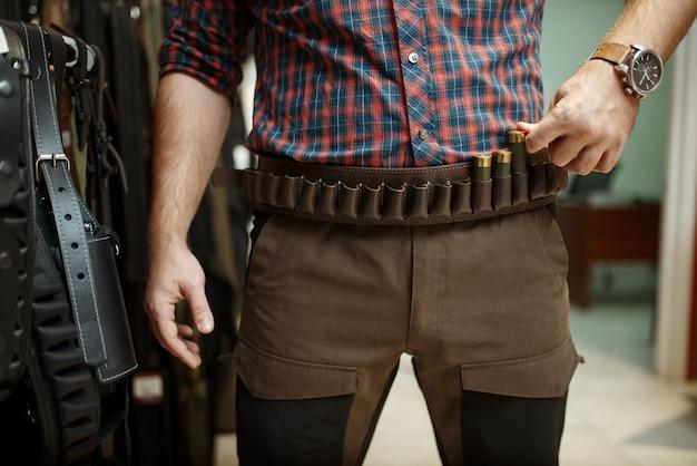 Man die munitieriem en uniform kiest voor de jacht in de wapenwinkel.