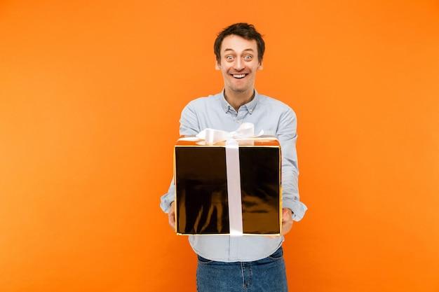 Man die naar de camera kijkt met een grappig gezicht en grote ogen met een grote gouden doos met een witte strikknoop