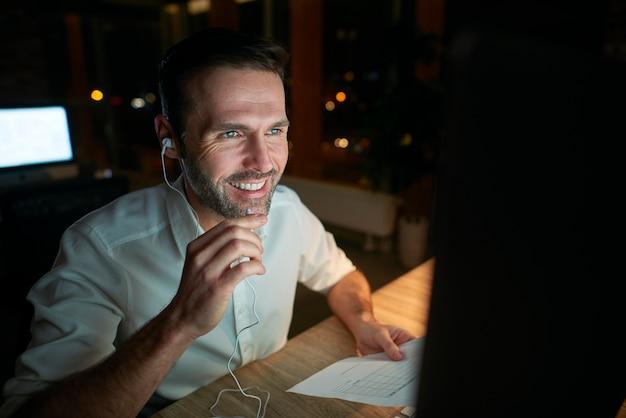Man die naar muziek luistert en laat in zijn kantoor werkt