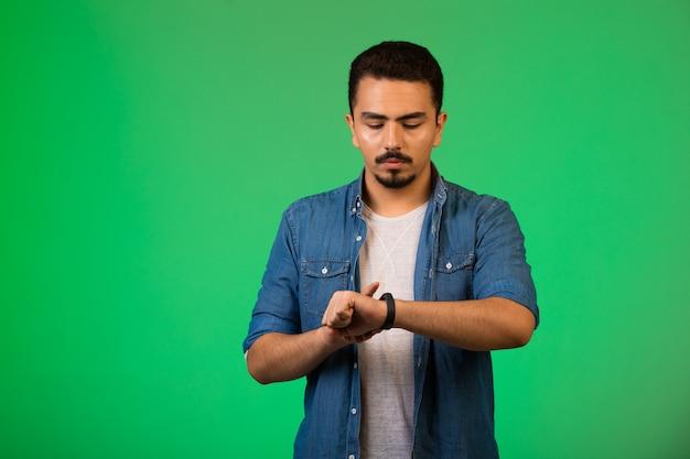 Man die naar zijn horloge kijkt en de tijd op een rustige manier controleert.