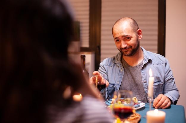Man die naar zijn vrouw kijkt terwijl hij een romantisch diner heeft en een glas met rode wijn vasthoudt. praten gelukkig zittend aan tafel eetkamer, genietend van de maaltijd thuis met romantische tijd bij kaarslicht.
