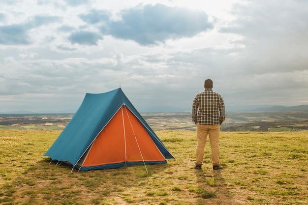 Man die naast de tent staat