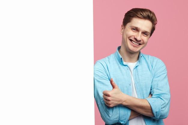 Man die naast een lege witte reclamebordmuur staat en duim omhoog laat zien