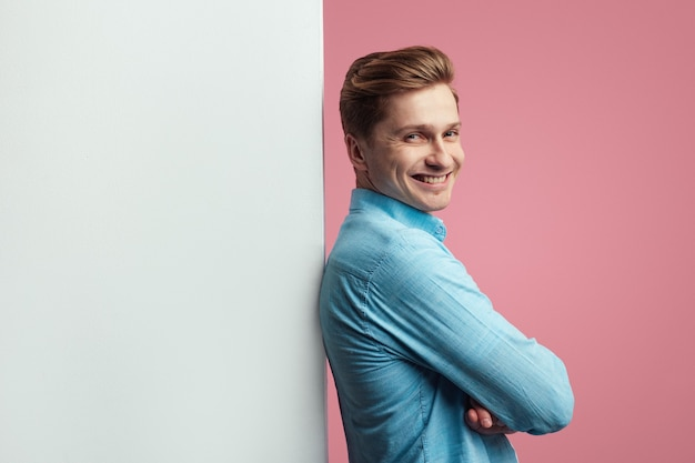 Man die naast een lege witte reclamebordmuur staat en glimlacht