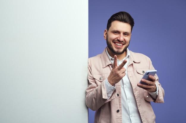 Man die naast een lege witte reclamebordmuur staat en vredesgebaar toont