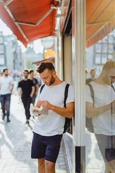Man die nederlandse wafels in de straat dichtbij koffie eet. straatvoedsel in holland.
