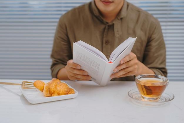 Man die ontbijt eet en een boek leest terwijl hij aan een witte tafel zit