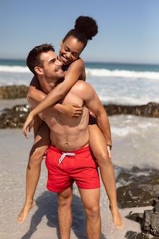 Man die op de rug aan vrouw op strand in de zonneschijn geeft