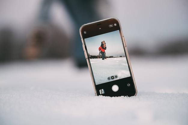 Man die op de rug rit geeft aan vriendin terwijl ze samen plezier hebben en selfie nemen met smartphone die op sneeuw in winterlandschap wordt geplaatst