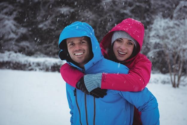 Man die op de rug rit geeft aan vrouw in het bos tijdens de winter
