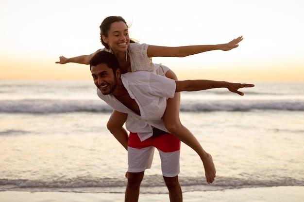 Man die op de rug rit geeft aan vrouw op het strand