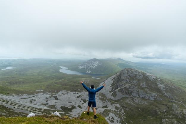 Man die op de top van de berg staat en zijn armen opheft in de berg errigal, co donegal, ierland