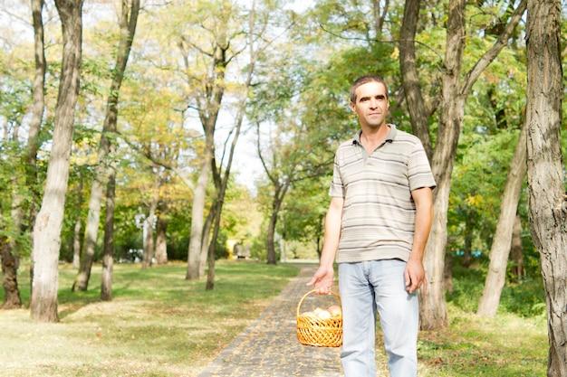Man die op een verhard voetpad door bos met een mandje met verse appels