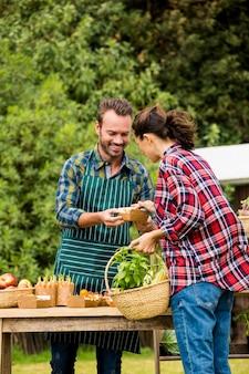 Man die organische groenten verkoopt aan vrouw