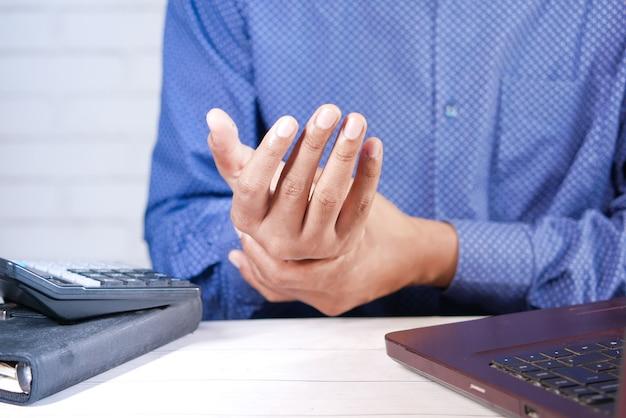 Man die pijn in de hand heeft terwijl hij aan het bureau werkt