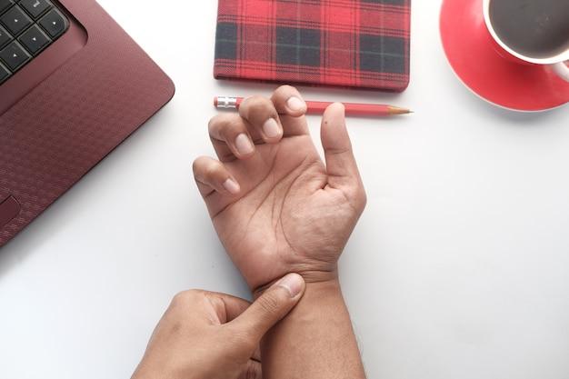 Man die pijn in de hand lijdt tijdens het werken op het bureau.
