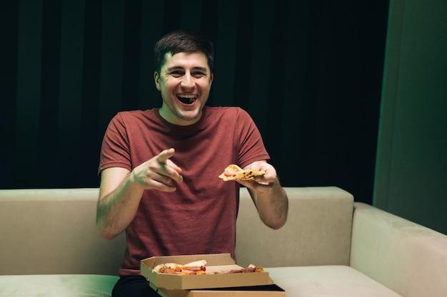 Man die pizza eet en favoriete komedie op tv kijkt