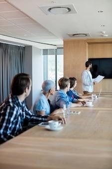 Man die presentatie geeft aan haar collega's in de vergaderruimte op kantoor