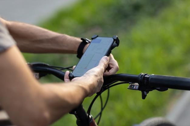 Man die route plant met behulp van gps-navigatietoepassing in mobiele telefoon op zijn fiets. apparaat aansluiten