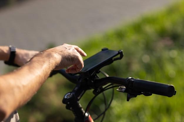 Man die route plant met behulp van gps-navigatietoepassing in mobiele telefoon op zijn fiets.