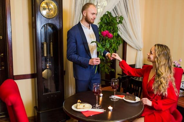 Man die rozen geeft aan vrouw in restaurant