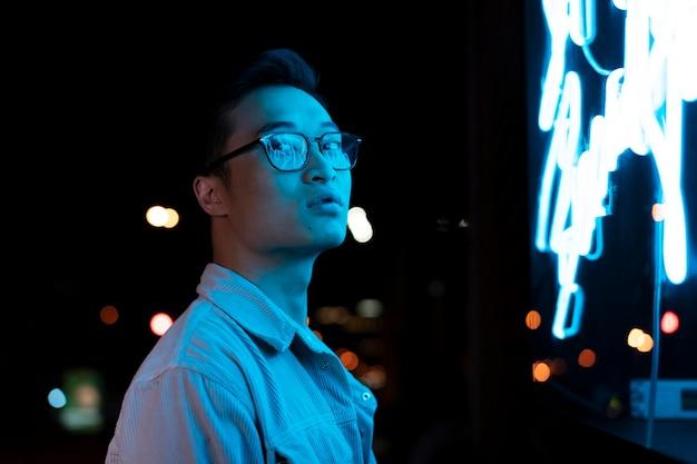 Man die 's nachts in blauw neonlicht poseert