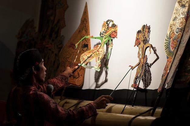 Man die schaduwpoppen speelt, centraal javaanse traditionele kunsten, indonesië